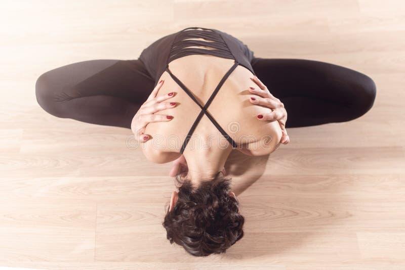 Vista superiore di bella parte posteriore della femmina Ginnasta in vestiti neri che si siedono allungando le gambe che piegano i immagine stock
