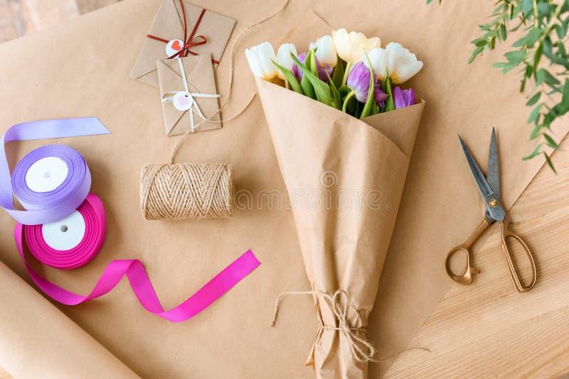 vista superiore di bello mazzo dei tulipani, delle forbici, dei nastri e delle buste con la corda immagine stock