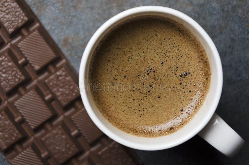 Vista superiore di caffè caldo con la grande barra di cioccolato e della schiuma, primo piano Spuntino dolce e rilassarsi tempo immagine stock libera da diritti