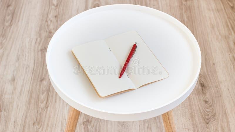 Vista superiore di carta per appunti in bianco vuota aperta con la penna rossa sulla tavola di legno del giornale rotondo bianco  fotografia stock libera da diritti