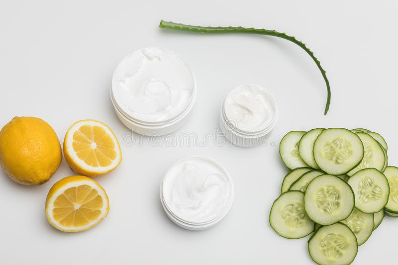 Vista superiore di crema facciale in contenitori, fette del limone e del cetriolo e pianta di vera dell'aloe fotografie stock