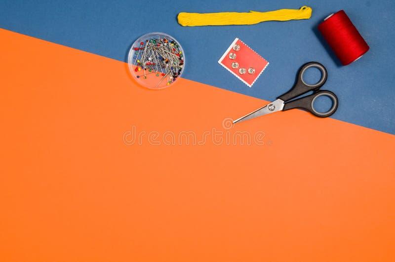 Vista superiore di cucito o di tricottare degli accessori sopra fondo blu immagine stock libera da diritti