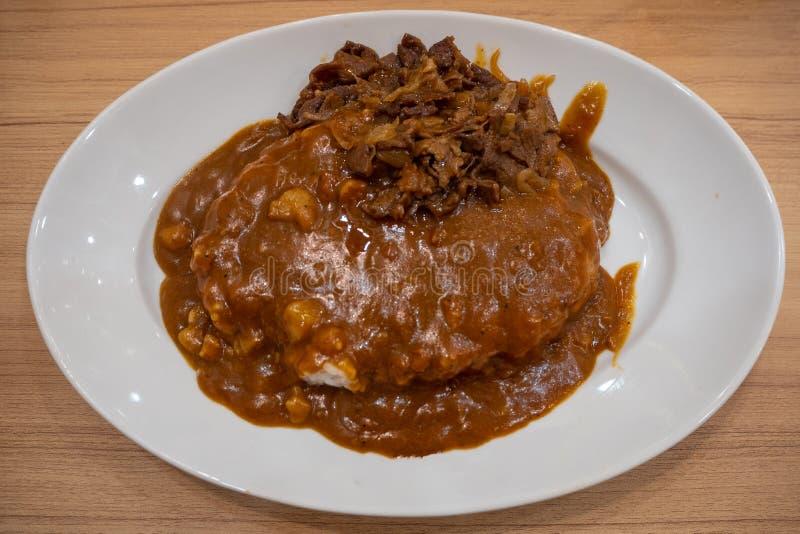 Vista superiore di curry giapponese completata su riso in piatto bianco sulla tavola di legno fotografia stock
