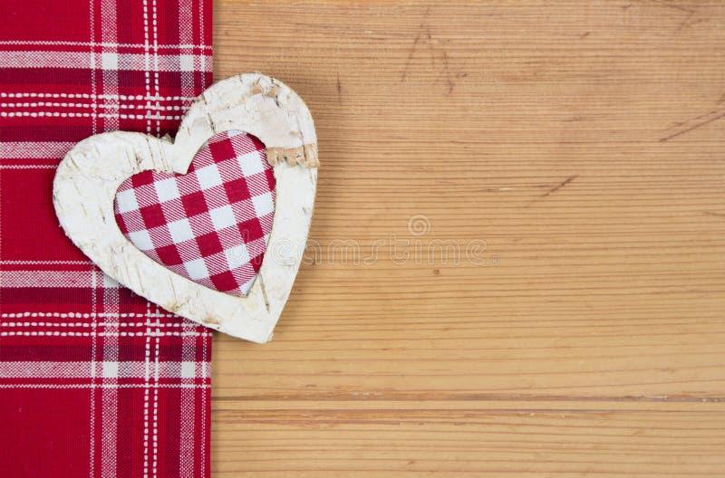 Vista superiore di forma a quadretti rossa del cuore su un vecchio backgroun di legno fotografie stock