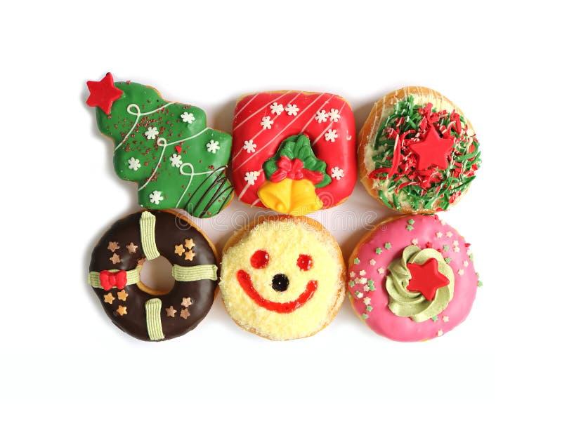Vista superiore di molti dolci delle ciambelle decorati Natale variopinto isolati su fondo bianco fotografia stock