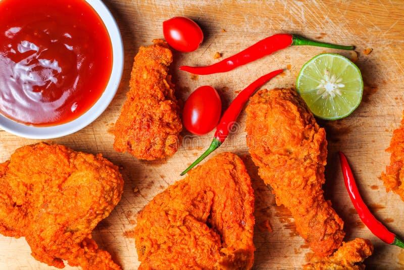 Vista superiore di pollo fritto piccante con i pomodori, il peperoncino rosso, la calce ed il ketchup sul vassoio di legno immagine stock libera da diritti