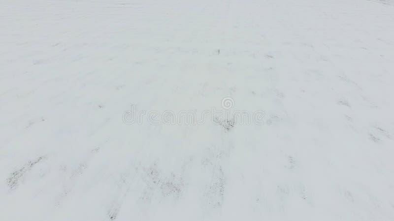 Vista superiore di un campo arato nell'inverno Un campo di grano nella neve fotografia stock