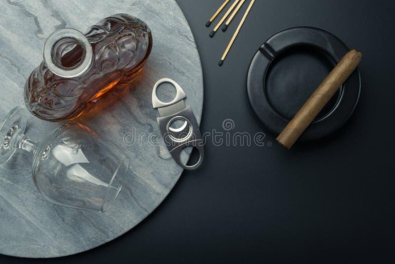 Vista superiore di un decantatore del brandy e di un vetro del bicchiere da brandy con una taglierina di sigaro di acciaio inossi immagine stock