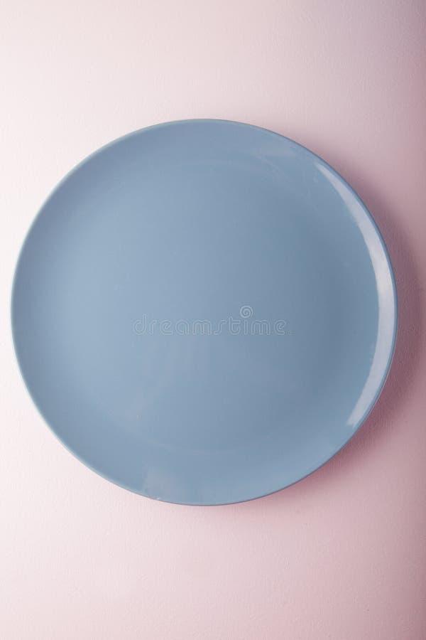Vista superiore di un piatto blu pastello su un fondo pastello della pesca Fotografia dell'alimento di minimalismo Stile geometri immagini stock libere da diritti