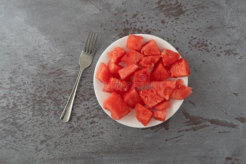 Vista superiore di un piatto dei bei pezzi dell'anguria con una forcella su una tavola chiazzata grigia immagine stock