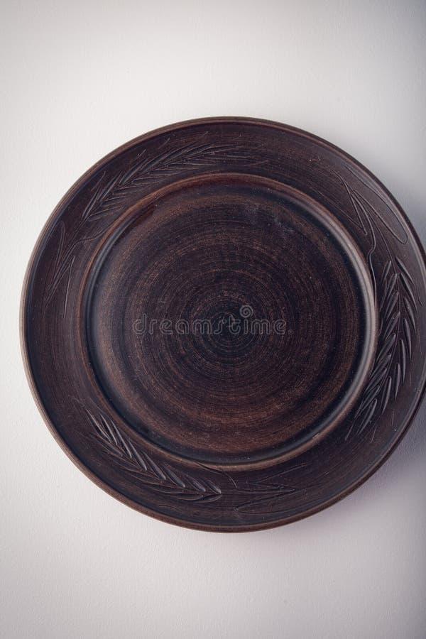 Vista superiore di un piatto di marrone scuro su un fondo bianco pastello Fotografia dell'alimento di minimalismo Stile geometric fotografia stock