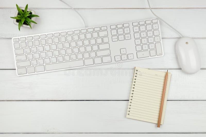 Vista superiore di un taccuino con la tastiera ed il topo sulla scrivania bianca fotografie stock libere da diritti