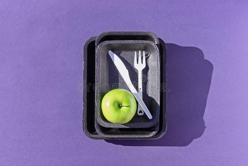Vista superiore di un vassoio di plastica vuoto con la mela verde sulla porpora immagine stock libera da diritti