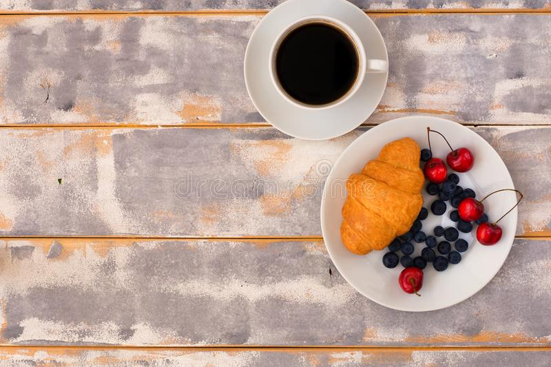 Vista superiore di una prima colazione deliziosa con i croissant, caffè e mirtilli e ciliegia sulla tavola fotografie stock
