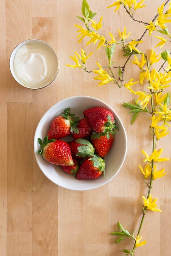 Vista superiore di una tavola di legno con la decorazione del fiore, ciotola di fragole rosse e fresche deliziose e di piccola ci fotografia stock libera da diritti