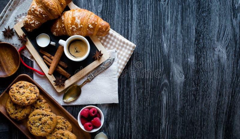 Vista superiore di una tavola di legno in pieno dei dolci, frutti, caffè, biscotti immagini stock