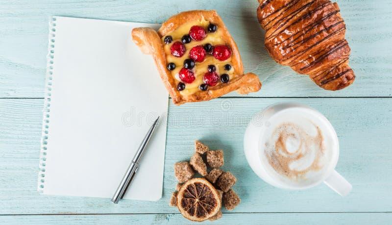 Vista superiore di uno spuntino dolce delizioso, di un caffè con latte e di uno strato per il vostro testo fotografie stock