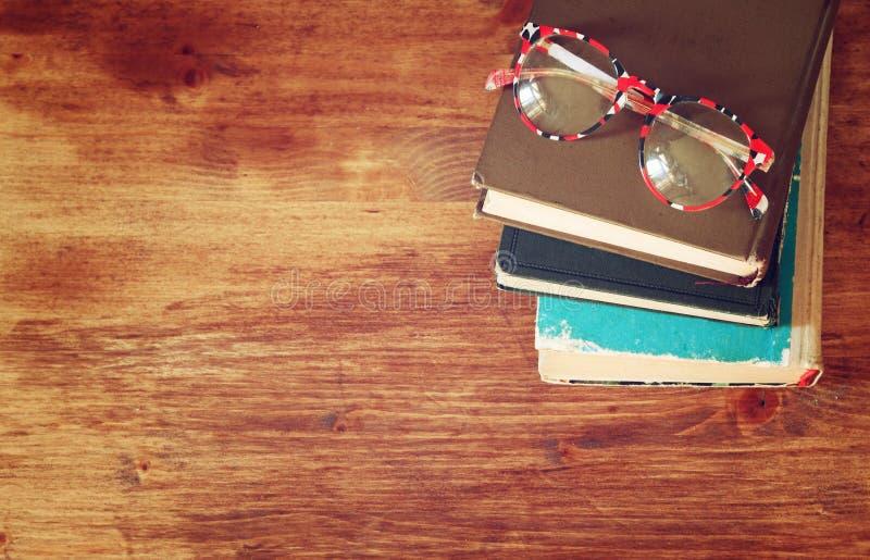 Vista superiore di vecchi libri su una tavola di legno retro immagine filtrata fotografie stock