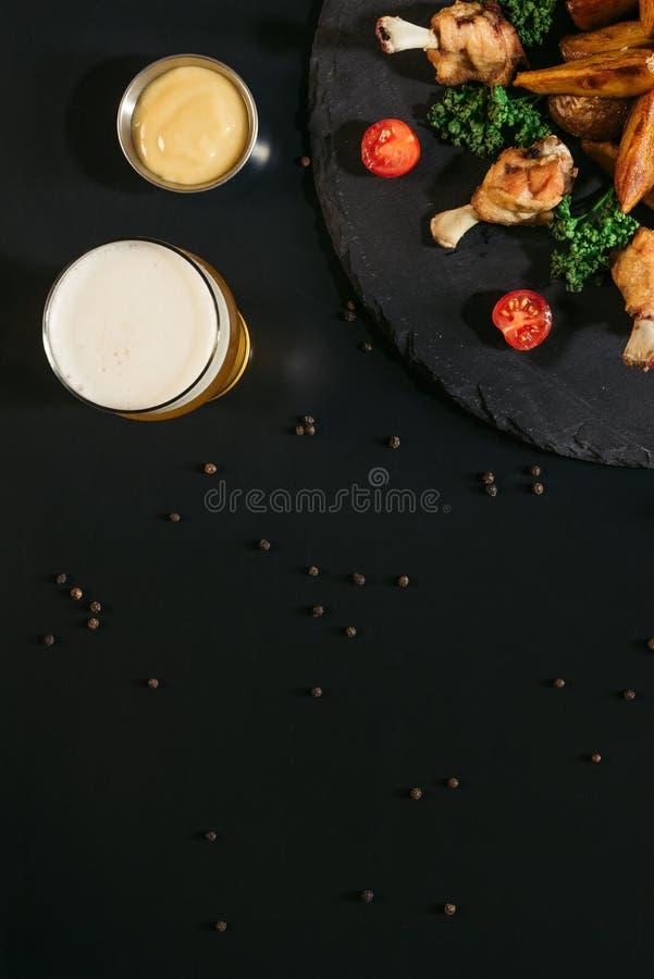 vista superiore di vetro di birra, di salsa e delle patate al forno saporite con le ali di pollo fritto fotografia stock libera da diritti
