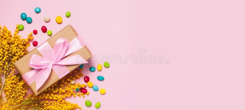 Vista superiore e disposizione piana del contenitore di regalo di Pasqua - fiori gialli della mimosa e dolci variopinti dell'uovo immagine stock