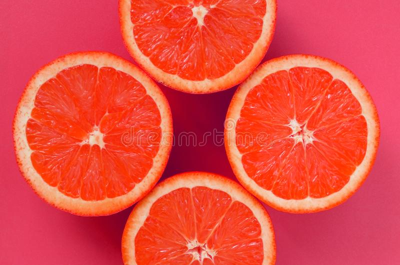 Vista superiore fette di parecchie di un pompelmo su fondo luminoso nel colore rosa Un'immagine saturata di struttura dell'agrume fotografia stock