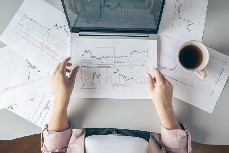 Vista superiore Giovane donna di affari che si siede alla tavola con la tazza di caffè e che lavora al computer portatile con i g immagini stock libere da diritti