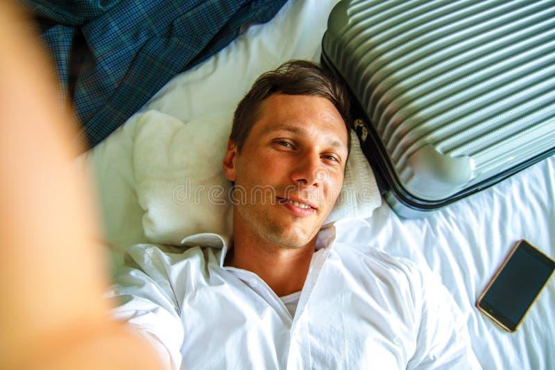 Vista superiore Giovane uomo d'affari che si rilassa sul letto dopo un giorno duro sul lavoro fotografie stock
