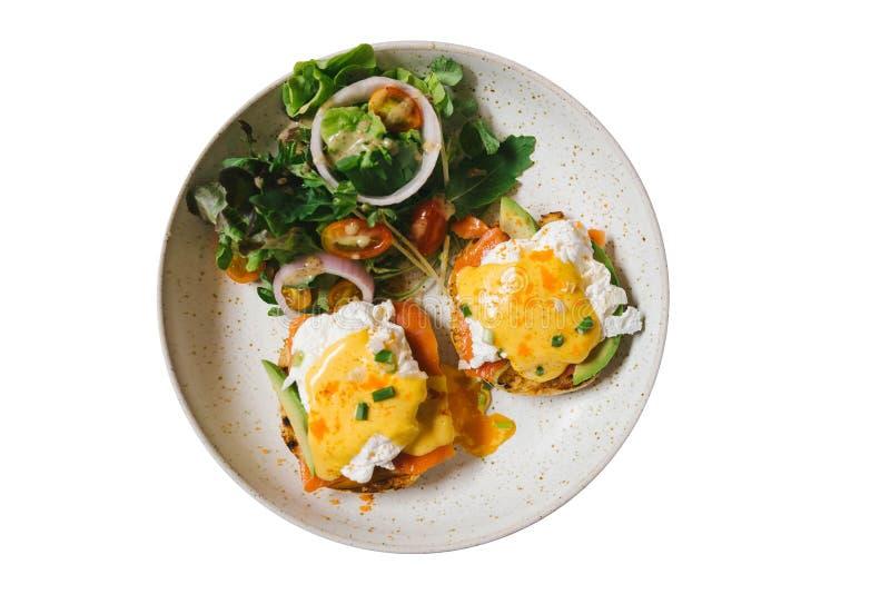 Vista superiore isolata dell'uovo alla benedict con il salmone e l'avocado, servita con insalata in piatto bianco fotografia stock libera da diritti
