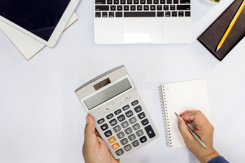 Vista superiore L'uomo facendo uso del calcolatore e la scrittura fanno la nota immagini stock
