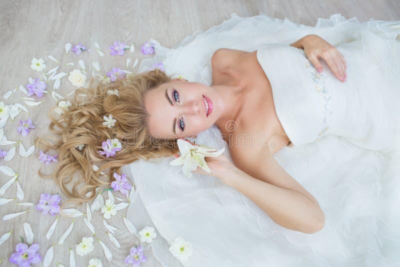 VISTA SUPERIORE: La sposa bionda caucasica si trova su un pavimento con i fiori di un campo immagine stock libera da diritti