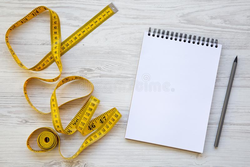 Vista superiore, nastro di misurazione giallo con il blocco note e matita su una tavola di legno bianca fotografia stock libera da diritti