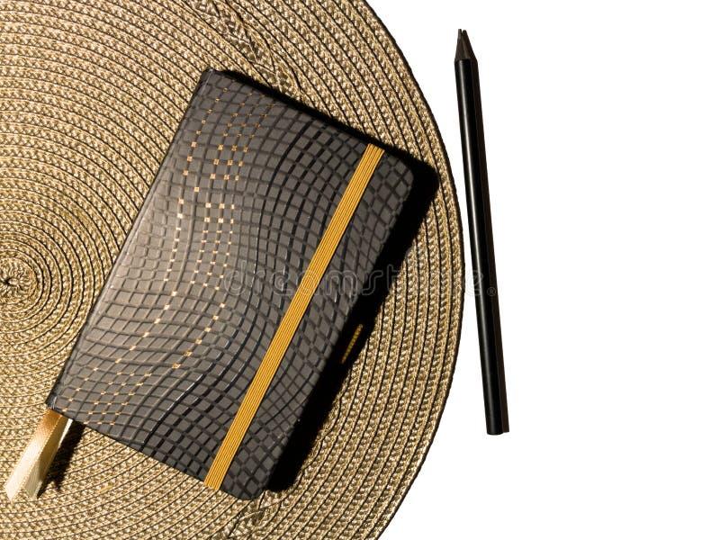 Vista superiore o vista o concetto piana dell'organizzatore chiuso con la matita nera che si trova sul cuscinetto grigio rotondo  immagini stock libere da diritti