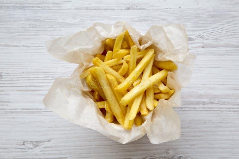 Vista superiore, patate fritte sopra la tavola di legno bianca immagine stock
