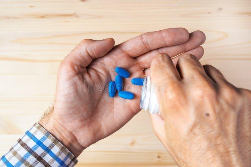 Vista superiore POV dell'uomo adulto che prende le pillole blu immagini stock libere da diritti