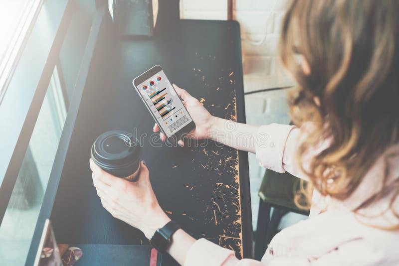 Vista superiore Primo piano dello smartphone e della tazza di caffè in mani della ragazza dei pantaloni a vita bassa che si siedo immagine stock