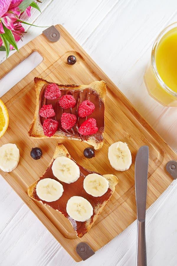 Vista superiore su pane tostato con burro di arachidi ed i lamponi, banana La composizione nella prima colazione pone pianamente  fotografia stock