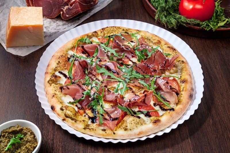 Vista superiore su pizza con il pomodoro, il parmigiano ed il prosciutto di Parma con besciamella con i ingridients sulla tavola  fotografia stock