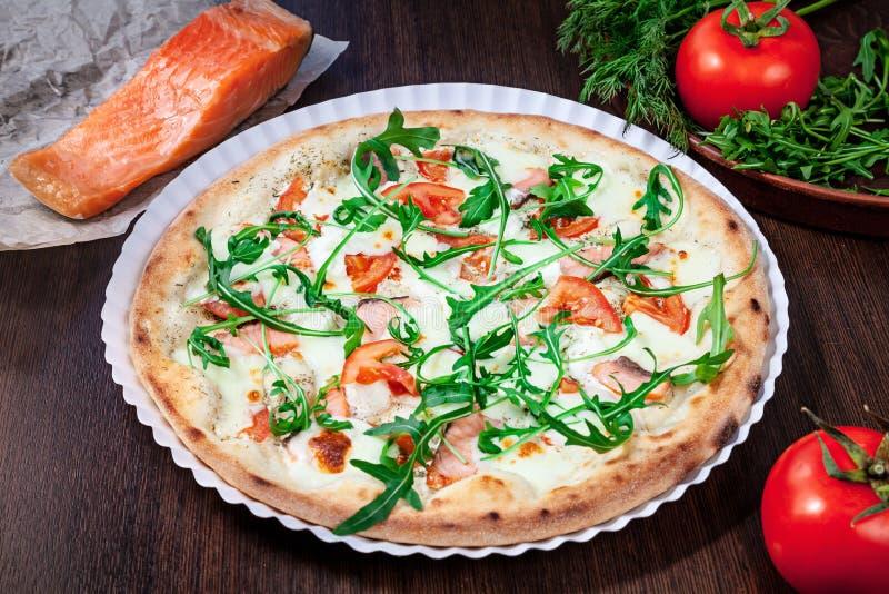 Vista superiore su pizza con il pomodoro, il parmigiano ed il salmone con besciamella con i ingridients sulla tavola di legno mar immagine stock