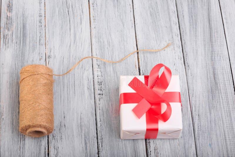 Vista superiore su una palla dei fili e di un contenitore di regalo sui precedenti di legno immagini stock libere da diritti