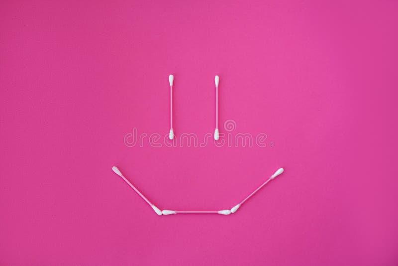 Vista superiore sui germogli rosa del cotone con le teste bianche presentate nella forma del fronte di sorriso su un fondo rosa immagini stock libere da diritti