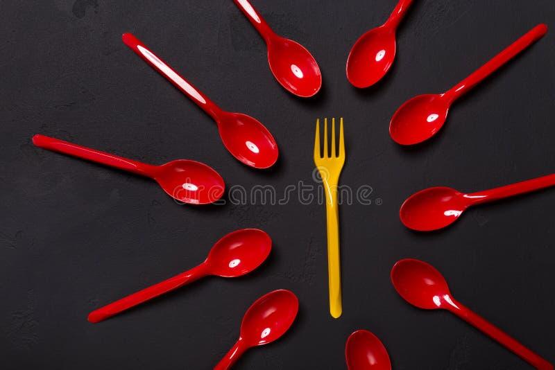 Vista superiore sulla forchetta e sui cucchiai di plastica su fondo nero immagine stock