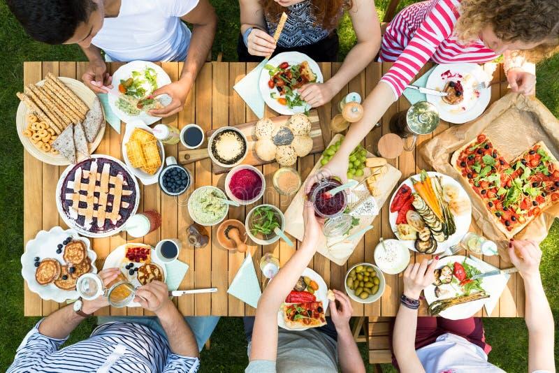 Vista superiore sulla gente che mangia pizza, pasticceria ed insalata durante la griglia p immagine stock