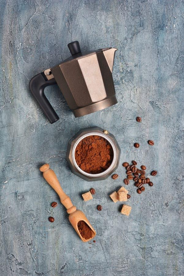 Vista superiore sulla macchinetta del caffè aperta del geyser con caffè macinato ed i fagioli per il caffè espresso di mattina immagini stock