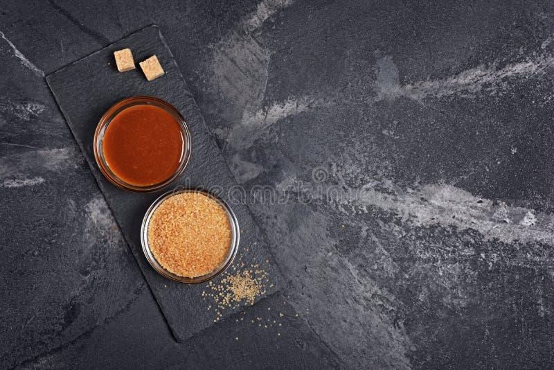 Vista superiore sulla salsa dolce casalinga del caramello in ciotola di vetro e zucchero di canna marrone fotografia stock