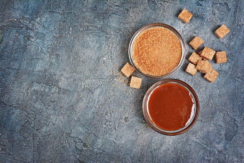 Vista superiore sulla salsa dolce casalinga del caramello in ciotola di vetro e zucchero di canna marrone immagine stock
