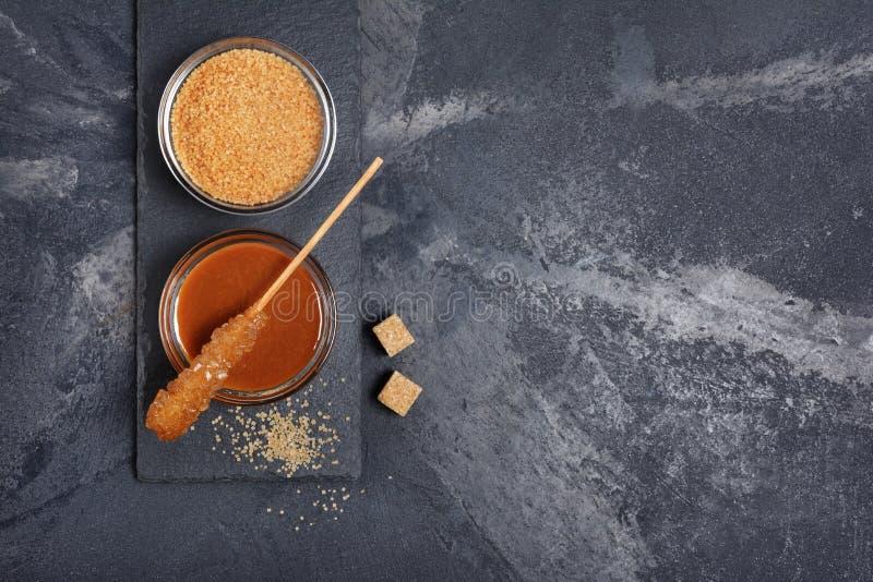 Vista superiore sulla salsa dolce casalinga del caramello in ciotola di vetro e zucchero di canna marrone con il bastone a crista fotografia stock libera da diritti
