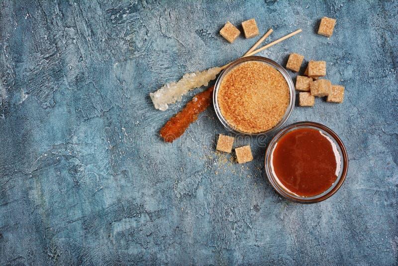 Vista superiore sulla salsa dolce casalinga del caramello in ciotola di vetro e zucchero di canna marrone con il bastone a crista fotografia stock