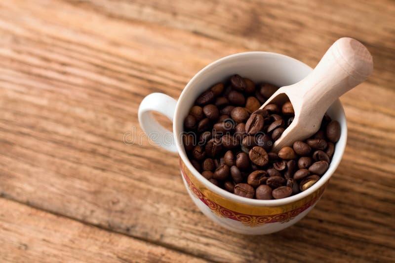 Vista superiore sulla tazza in pieno dei chicchi di caffè immagine stock