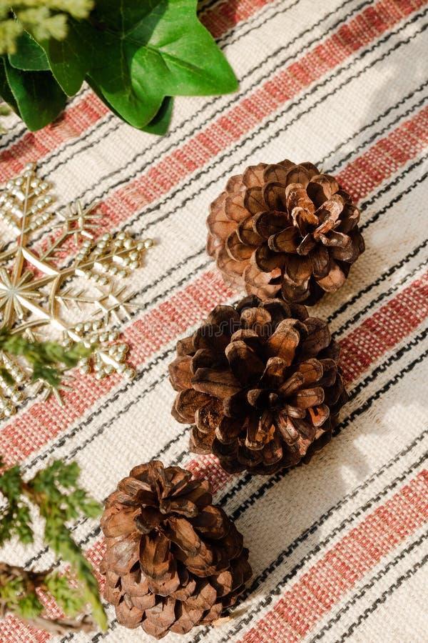 Vista superiore sulle pigne dell'albero con le decorazioni di Natale su un asciugamano bianco e rosso fotografie stock libere da diritti