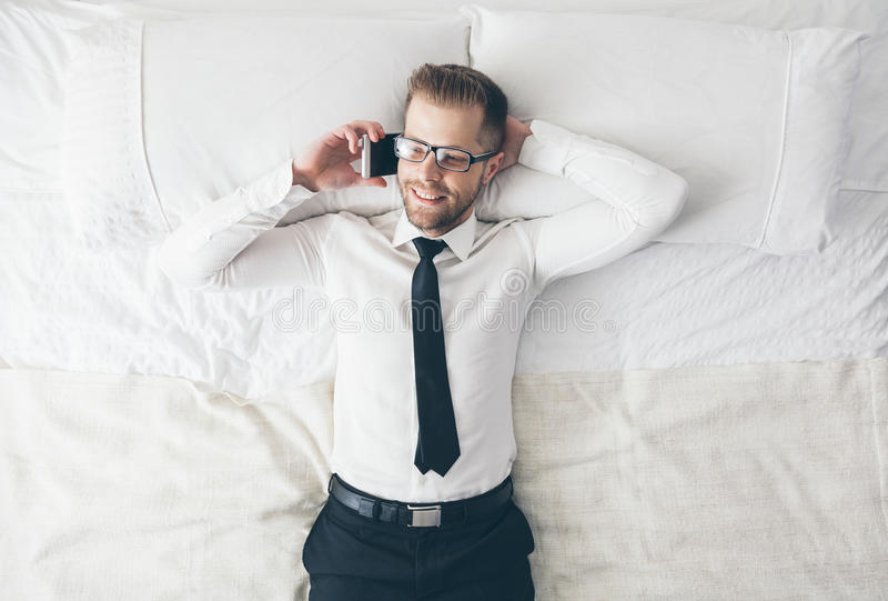 Vista superiore Uomo d'affari bello con i vetri che si trovano sul letto fotografie stock